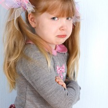 young girl with long blonde hair tied up looking upset, with pouting lip and arms folded in a grey and pink jumper the authentic eclectic garrulous glaswegian medium