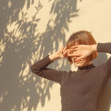 Woman with bob and bangs holds hands face outward over her eyes. She stands against a cream background decorated with gray leaf shadows.