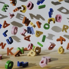 Conceptual image of colourful falling letters, casting shadows on a white wall.