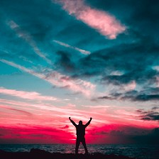"""A person standing on a beach at sunset with both hands raised in a """"Rocky"""" pose."""