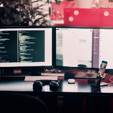 Two monitors with code on a desk