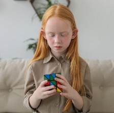 Little girl solving a rubric's cube and exercising her brain
