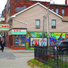 """Photograph of the facade of the convenient store, """"Kim's Convenience"""" for the CBC show by the same name. There is a poster of the Kim family on the side of the store and two signs that say """"Kim's Convenience"""" in green, white, and blue."""