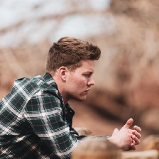 A man in plaid leans on a fence while looking into the distance, pensive