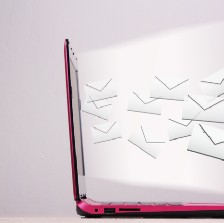 A laptop open and facing right with little envelopes flying out.