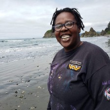 Short story and poetry collection by Aigner Loren Wilson article cover. Picture of author smiling on a beach. Behind her are rocky and tree ridden cliffs and the rolling ocean. Speculative fiction by Aigner Loren Wilson. Horror by Aigner Loren Wilson