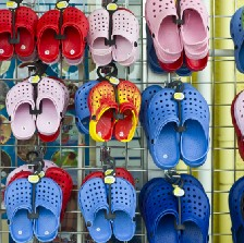 A variety of colorful Crocs brand foam slippers on display for sale.