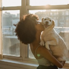 Black woman kissing her medium sized dog, who she's holding in her arms, in front of a window. Calm, peaceful, happy.