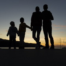 The silhoutte of a family holding hands at sunset.