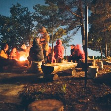A group of people in the woods sitting around a campfire