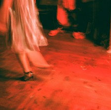 Artsy photograph with blurred red tones. The focus is on a woman's skirt and legs. There's another person's legs in the photograph too. Possibly people on stage or dancing.