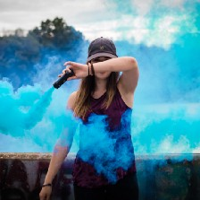 Standing woman in baseball cap with arm in front of her face is setting off a blue smoke bomb. Blue smoke fills the frame. Trees in the background.