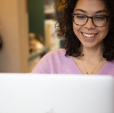 A woman smiles at her laptop screen.