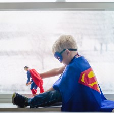 Little boy dressed like Superman, playing with Superman action figure.