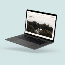A Macbook Pro displaying a real estate website hovers in front of a solid light blue background.