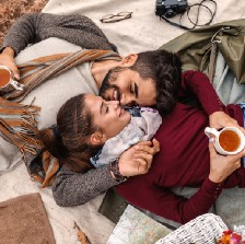 Couple lie together on rug with cups of miso soup