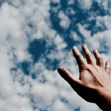 Hand reaching for the clouds.