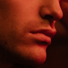 A red light shining on the lower half of a man's face.