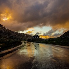A rain-soaked road leading to a wooden hose on a hill surrounded by mountains and a cloudy sky.