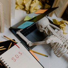 Skeleton collapsed on laptop at desk with SOS written on pad.