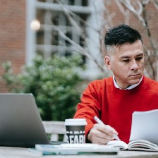 A man with buzzcut hair looking at a stack of papers outdoors