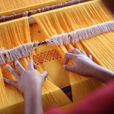 a loom with yellow threads and a woman's hands