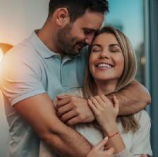 Couple hug in front of lamp