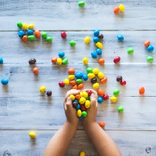 Child's hands holding jelly beans. Quite a few jelly beans spread across a light colored wooden surface.