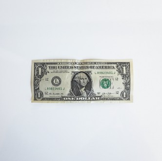 A photo of a US 1-Dollar bill sitting face-up on a flat, white surface.