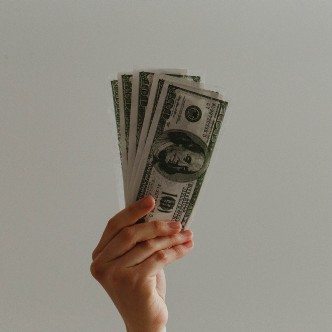 Photo of a hand holding up money.