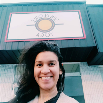 Photograph of Simi Burn, co-founder of Tulsa, Oklahoma's Sun People Yoga, standing in front of the studio.