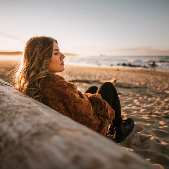 Woman leaning on a log at the beach.