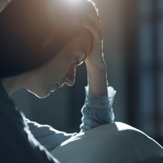 A woman cradles her head in her hand and looks down in sadness.