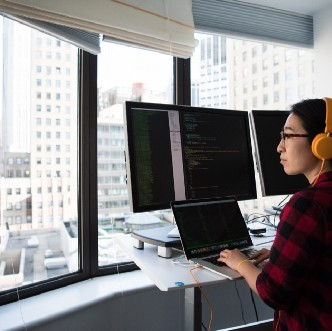 photo of a programmer with multiple screens looking out of an apartment window