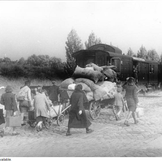 Women and children carrying possessions to trains circa 1946