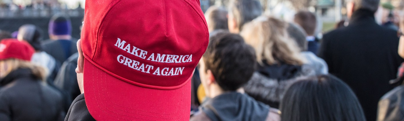 """A young man at a Donald Trump rally wears a """"Make America Great Again"""" hat."""