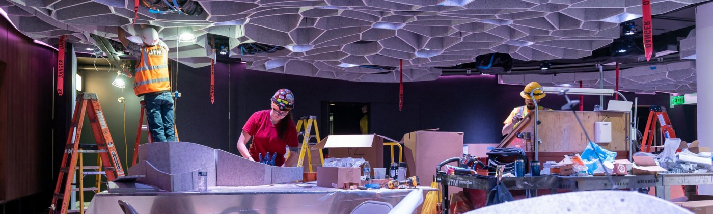 People wearing hard hats install the honeycomb ceiling of the Octave 9 recital hall.