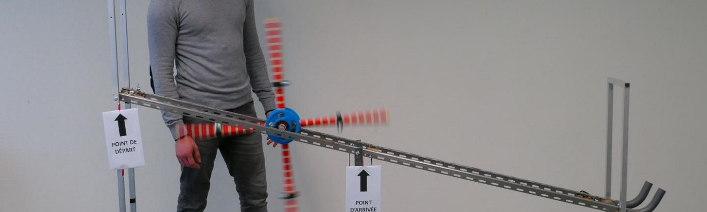 A person watches a spoked, weighted wheel roll down an incline.