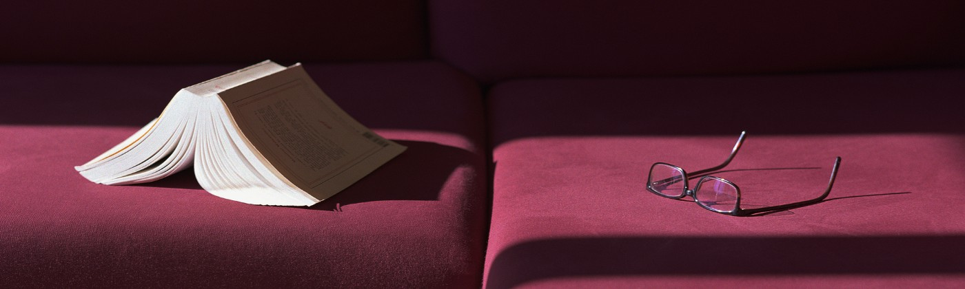 Book and eyeglasses left on a maroon velvet couch.