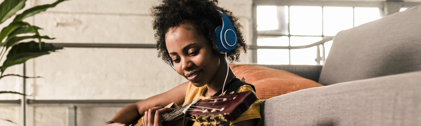 A Black woman learning to play the guitar from an online video.