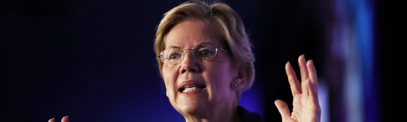 A photo of Elizabeth Warren with her hands raised.