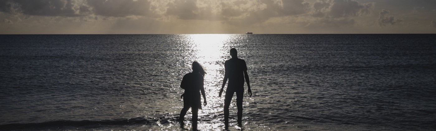 Two people wading into a large body of water, backlit by the setting sun.