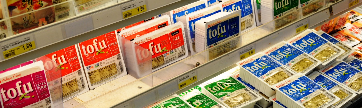 A grocery store refrigerated shelf stocked with many tubs of tofu—firm, extra-firm, and silken in different colors