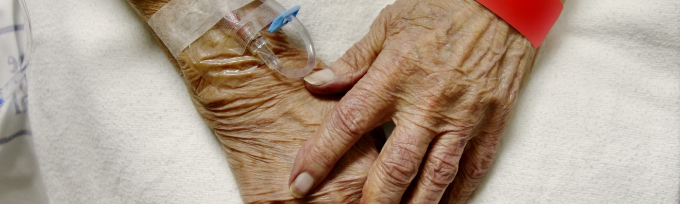 An elderly woman's hands with IVs and hospital bracelets.