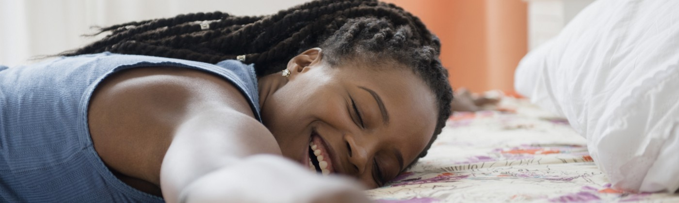 A woman smiling and hugging her bed.