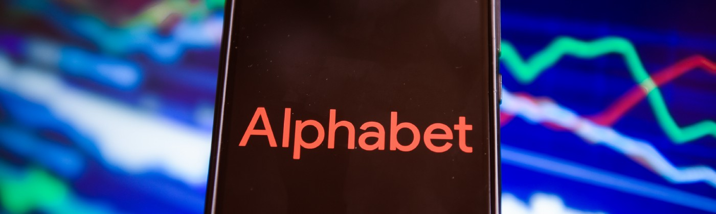 In this photo illustration an Alphabet logo seen displayed on a phone against a background illustrating the stock market.