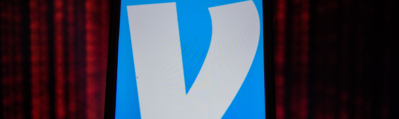 A logo of Venmo displayed on a phone screen against a dark red background, signifying privacy, technology, and transactions.