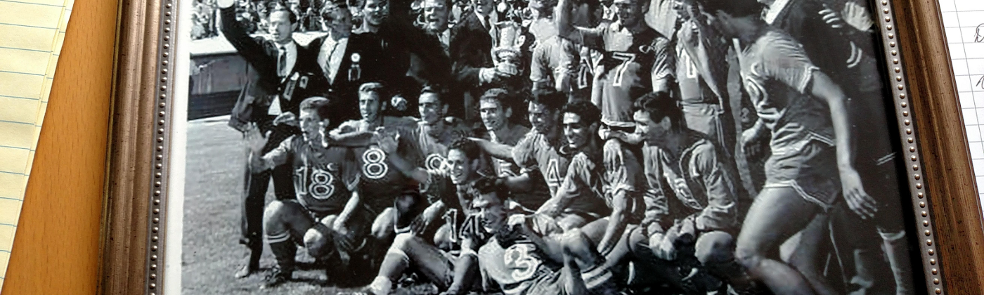 A framed black-and-white photo of a group of athletes posing and waving on a field.