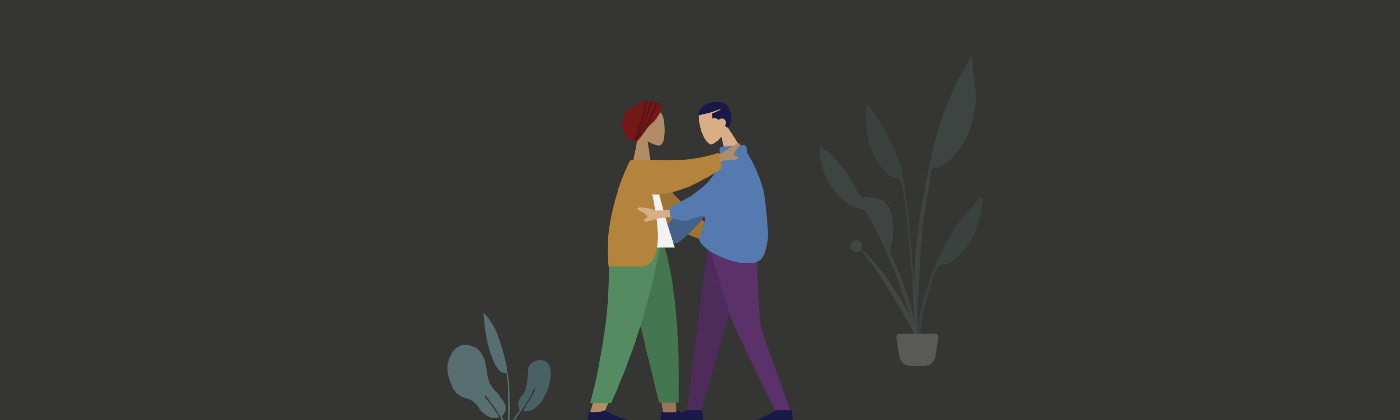 Two persons hugging each other. Plants in the background.