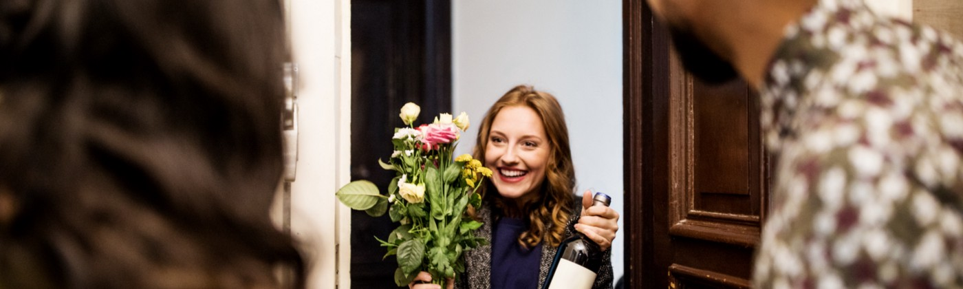 A woman holding a bouquet and a wine bottle in their neighbor's doorway.